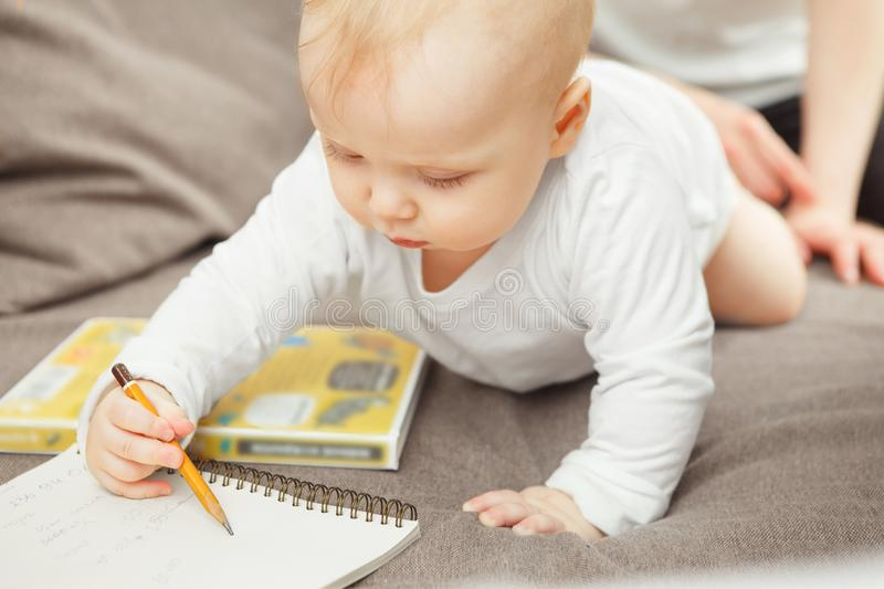 Concentrated young toddler learning draw. Baby hold pencil in hand. Concentrated young toddler learning to draw. Baby hold pencil in hand, lies on the stomach stock photography