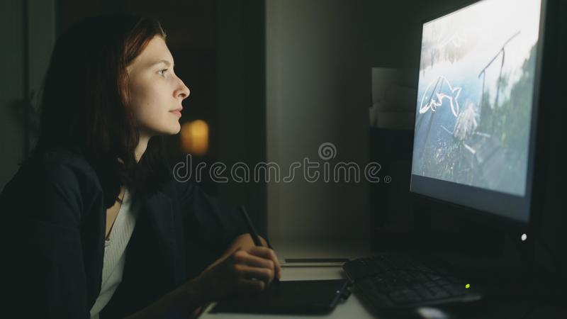 Concentrated young woman designer working in office at night using computer and graphics tablet to finish job royalty free stock image