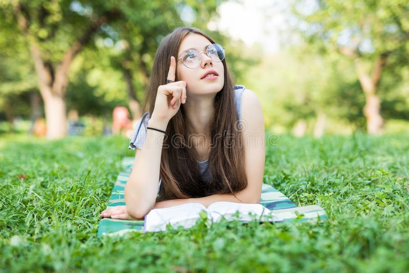 Concentrated young woman resting with book in park. Serious beautiful girl lying on grass while reading favorite romance. Dreaming stock image