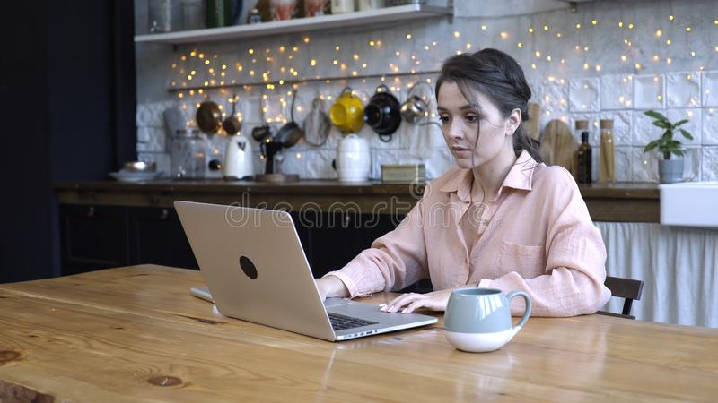Concentrated young woman sitting in the kitchen at wooden table and typing on her personal silver laptop with the cup of stock photo