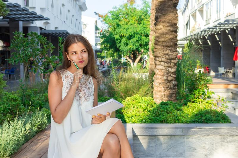 Concentrated young woman thinking and making notes in notepad during free time sitting outdoors on the bench.  royalty free stock images