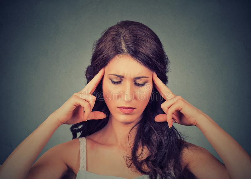 Concentrating beautiful woman holding fingers on temples royalty free stock image