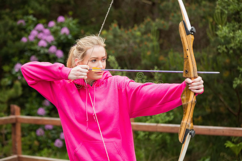 Concentrating blonde practicing archery. At the range royalty free stock photos