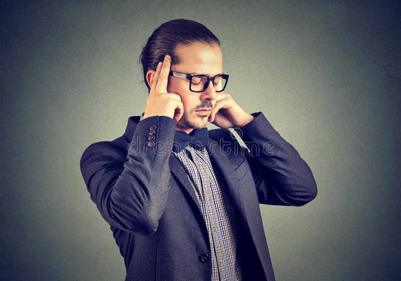 Concentrating businessman holding fingers on temples stock image
