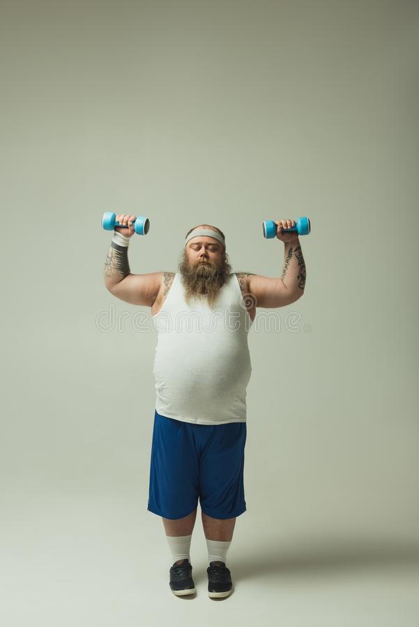 Peaceful thick guy training with sporty weights stock photography