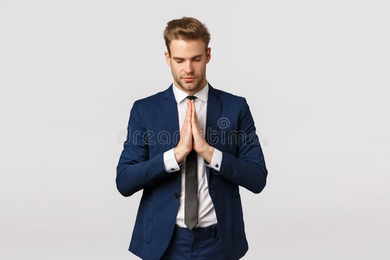Concentrating mind and soul. Peaceful and calm successful blond bearded businessman, young male entrepreneur in suit stock image