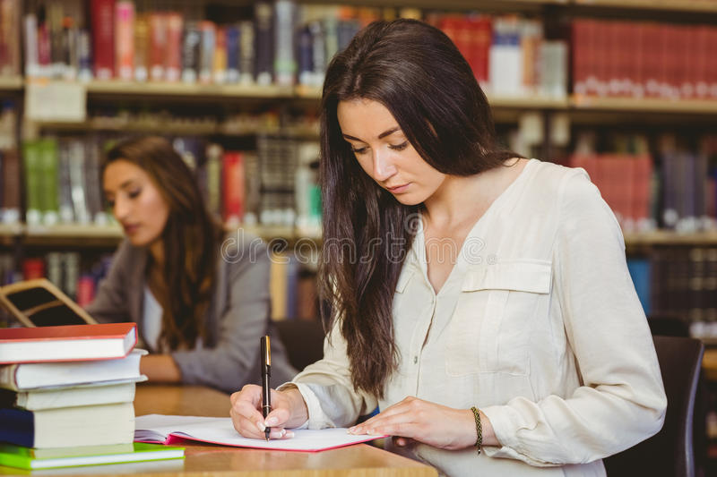Concentrating pretty brunette student writing in notepad royalty free stock image