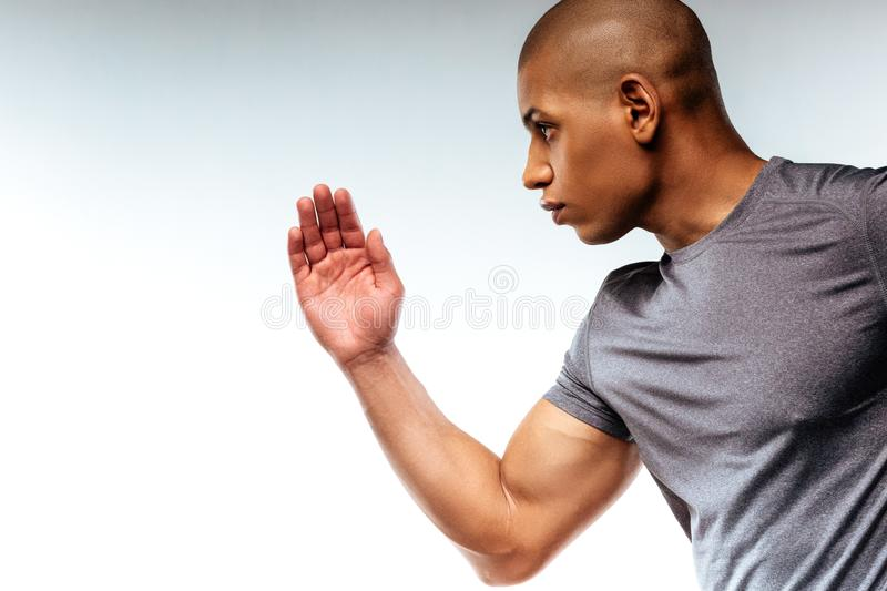Concentrated man demonstrating his power while doing sports. Concentration. A concentrated man demonstrating his power while doing sports stock images