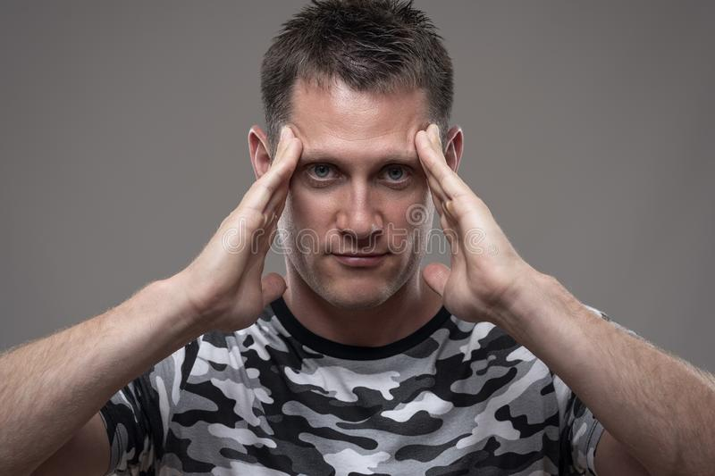 Concentration or focus concept. Young adult man with fingers on temples staring at camera. Over gray background royalty free stock image