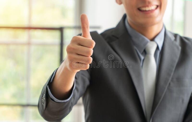 Concentration sélective des pouces. Un jeune homme d'affaires qui montre des pouces à la réussite. Concept de nouveau succès e images libres de droits