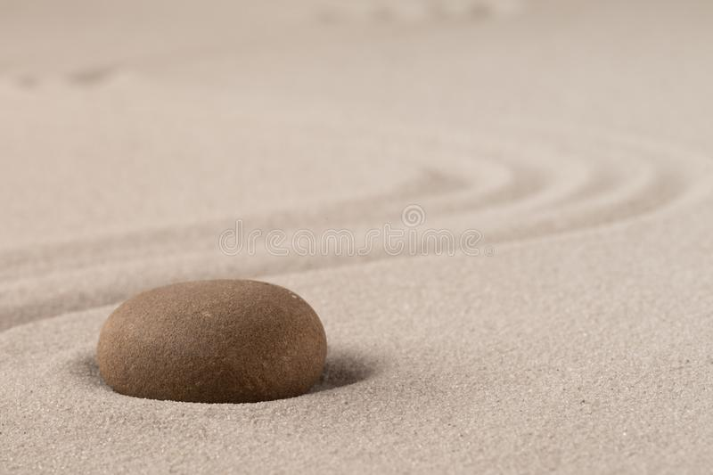 Concentration trough focus on a zen meditation stone. Round rock in sand texture background royalty free stock photos