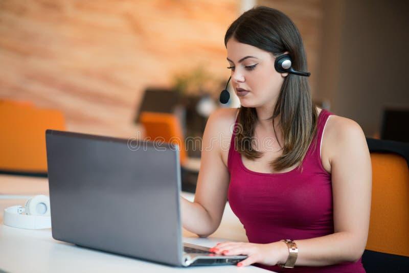 Concentrato sul lavoro Giovane bella donna che utilizza il suo computer portatile mentre sedendosi nella sedia al suo posto di la immagini stock