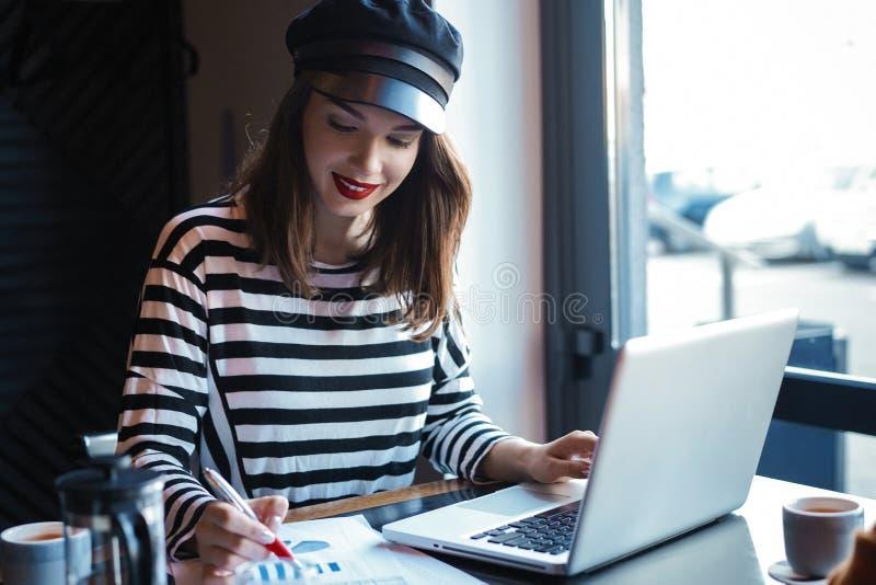 Concentrato sul lavoro Giovane donna sicura nell'abbigliamento casual astuto che lavora al computer portatile mentre sedendosi vi immagini stock libere da diritti