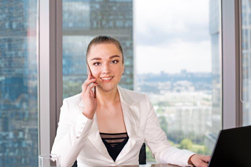 Concentrato sul lavoro Giovane donna sicura nell'abbigliamento casual astuto che lavora al computer portatile mentre sedendosi vi fotografia stock libera da diritti