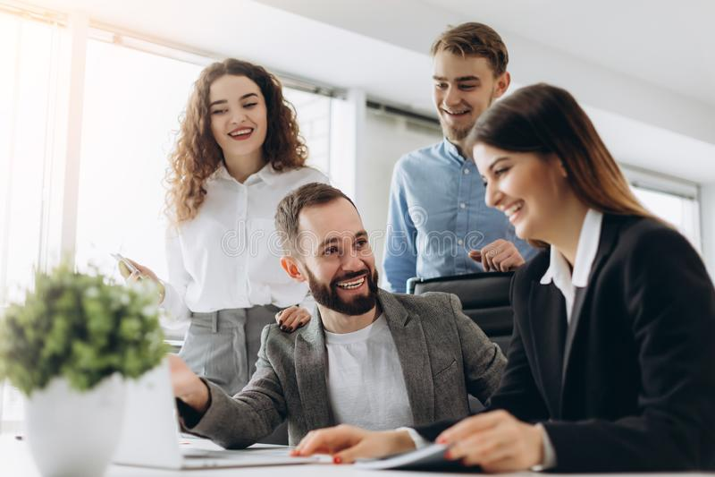 Concentrazione completa sul lavoro Gruppo di gente di affari che lavora e che comunica mentre sedendosi alla scrivania insieme fotografia stock libera da diritti