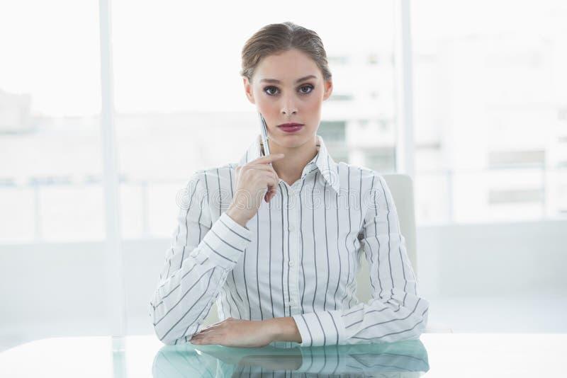 Concentrazione del pensiero di seduta della donna di affari elegante al suo scrittorio immagine stock libera da diritti