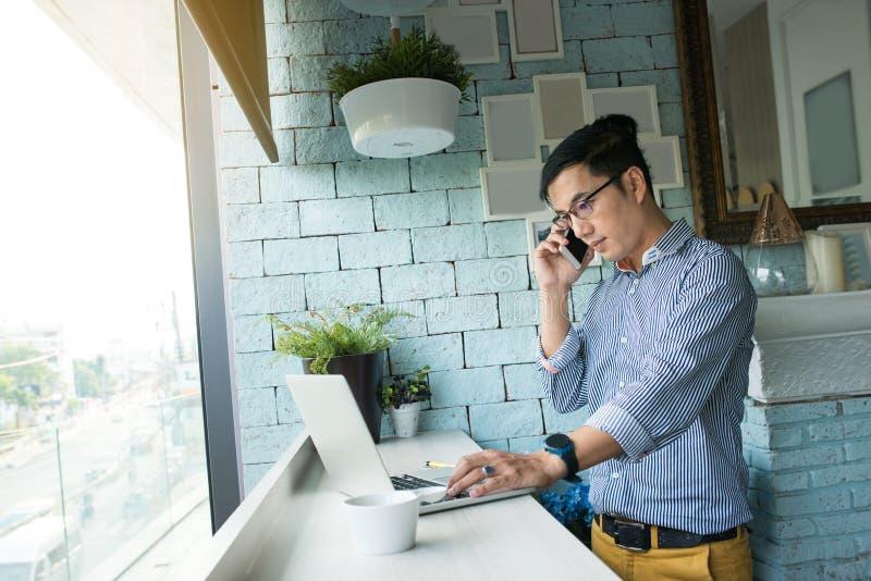 Concentre al hombre de negocios asiático joven en eyegla del desgaste de la ropa informal imágenes de archivo libres de regalías