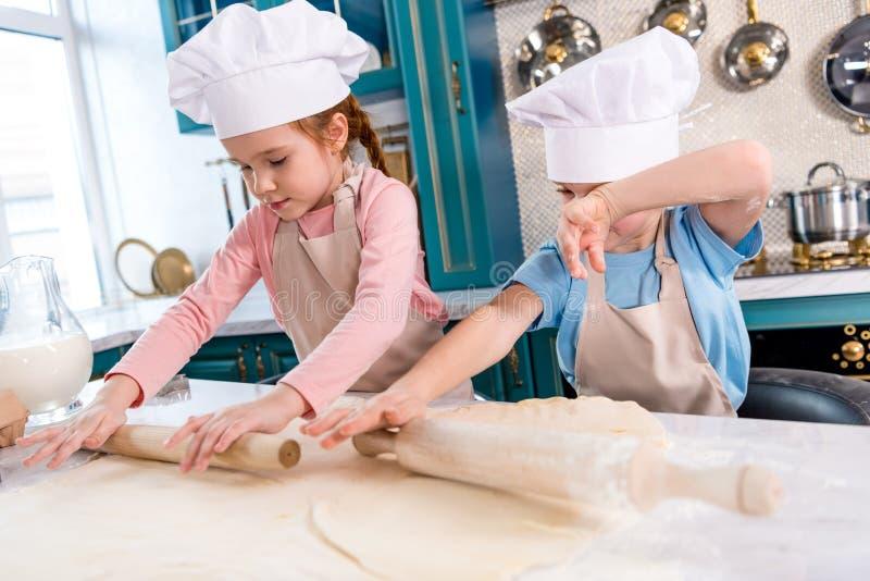 concentreerde kleine kinderen in chef-kokhoeden en schorten die deeg rollen stock foto's
