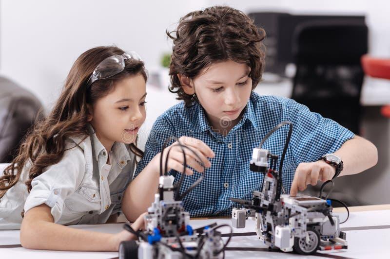 Concentreerde kleine wetenschappers die technologie-van les genieten op school stock afbeelding