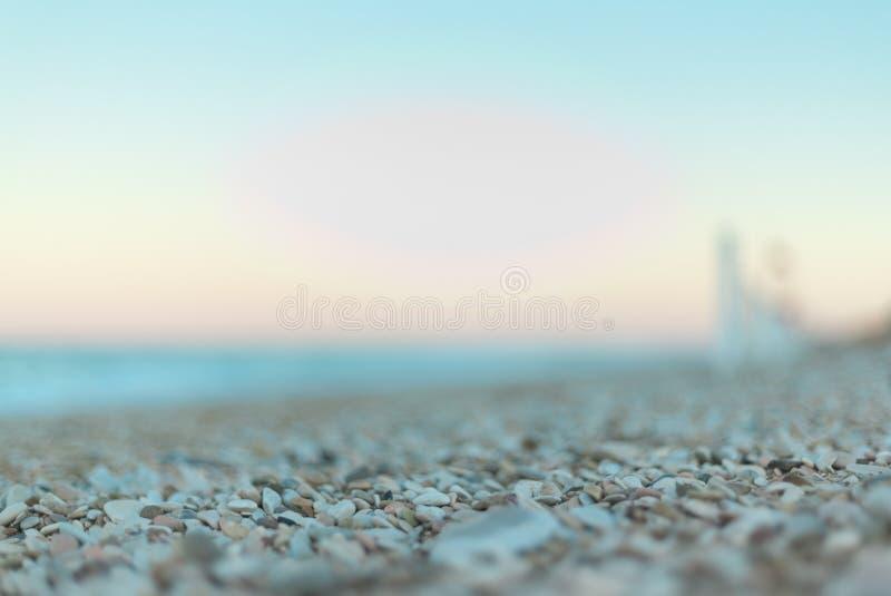 Concentrez le détail sur des pierres de lumière de matin sur la plage près du rivage photographie stock