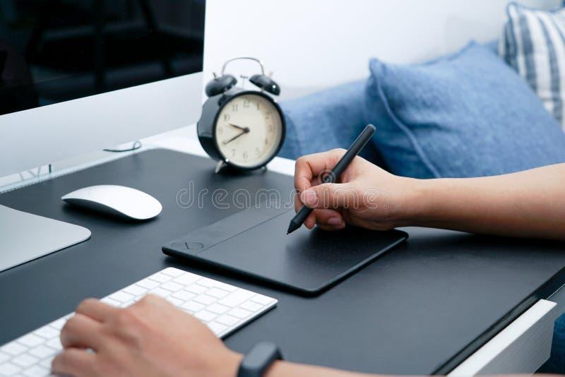 Concentrez sur le concepteur occupé travaillant sur l'ordinateur à côté de la souris numérique de stylo photos stock