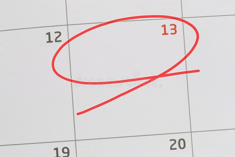 Concentrez sur le numéro 13 dans le calendrier et videz l'ellipse rouge image stock