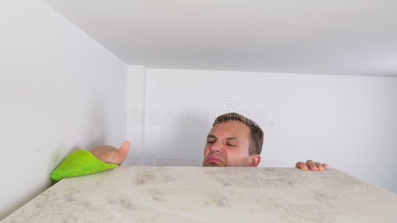Concept à la maison de nettoyage un homme essuie la poussière d'une haute armoire dans sa maison image stock