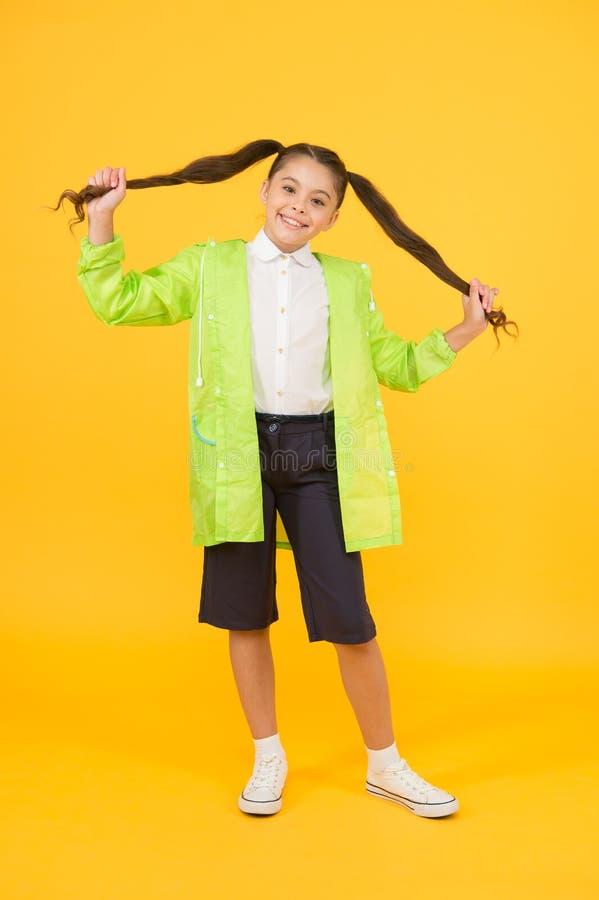 Concept étanche Enfant adorable Une bonne écolière porte un imperméable sur fond jaune Petite écolière portant de l'eau images stock