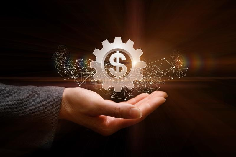 The concept is the ability of money operation. A businessman is holding a cogwheel in his hand with currency unit inside. The concept is the ability of money royalty free stock photography