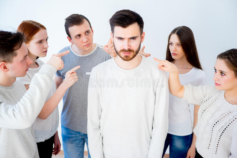 Concept of accusation. Group of people pointing at a man stock photo