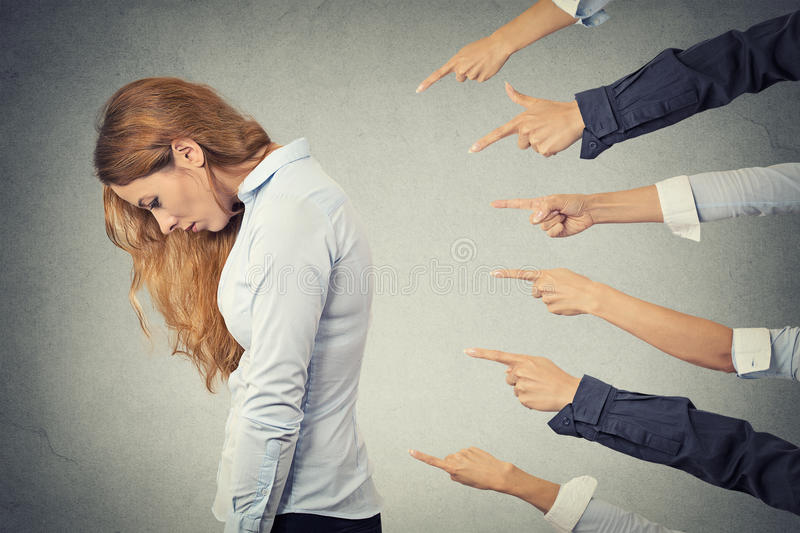 Concept of accusation guilty businesswoman person. Side profile sad upset woman looking down many fingers pointing at her isolated grey office background stock photo