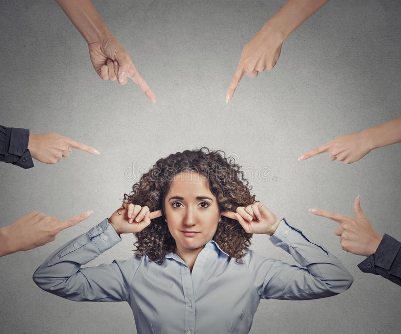 Concept of accusation of guilty businesswoman. Portrait unhappy sad upset woman plugging her ears many fingers pointing at her grey office background. Human royalty free stock photos