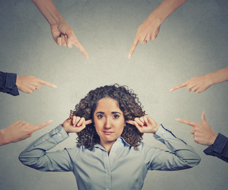 Concept of accusation of guilty businesswoman. Portrait unhappy sad upset woman plugging her ears many fingers pointing at her grey office background. Human royalty free stock images