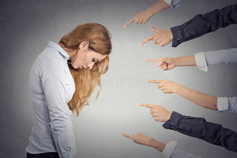 Concept of accusation of guilty businesswoman. Side profile portrait sad upset woman looking down many fingers pointing at her grey office background. Human royalty free stock photography