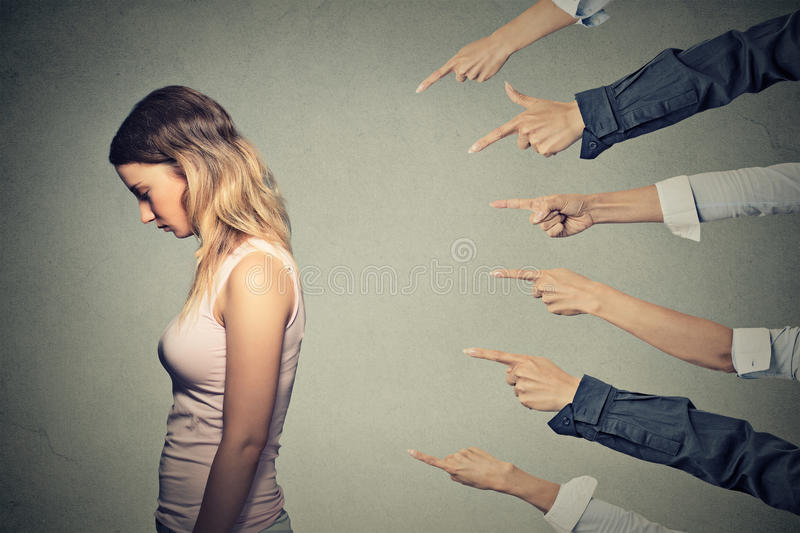 Concept of accusation guilty person girl. Side profile sad upset woman looking down many fingers pointing at her back isolated on grey office wall background stock photos