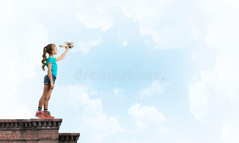 Concept achteloze gelukkige kinderjaren met meisje proef het dromen om te worden stock foto