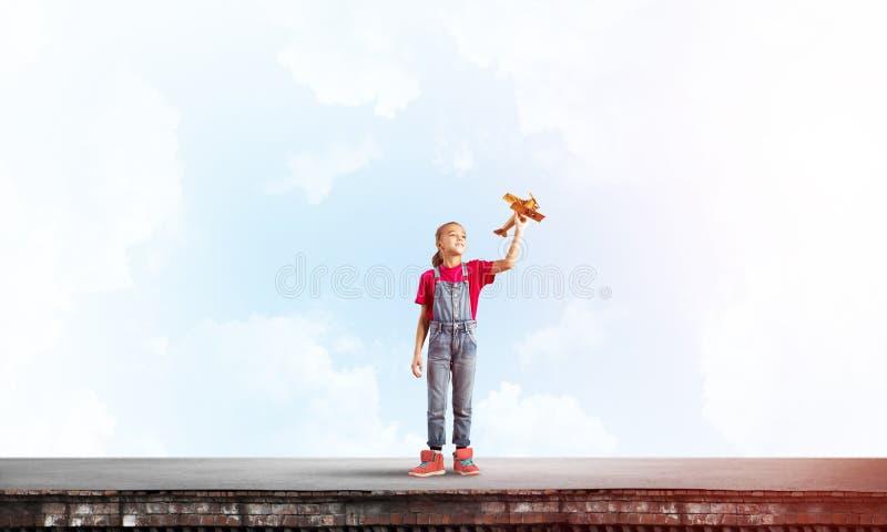Concept achteloze gelukkige kinderjaren met meisje proef het dromen om te worden royalty-vrije stock afbeelding