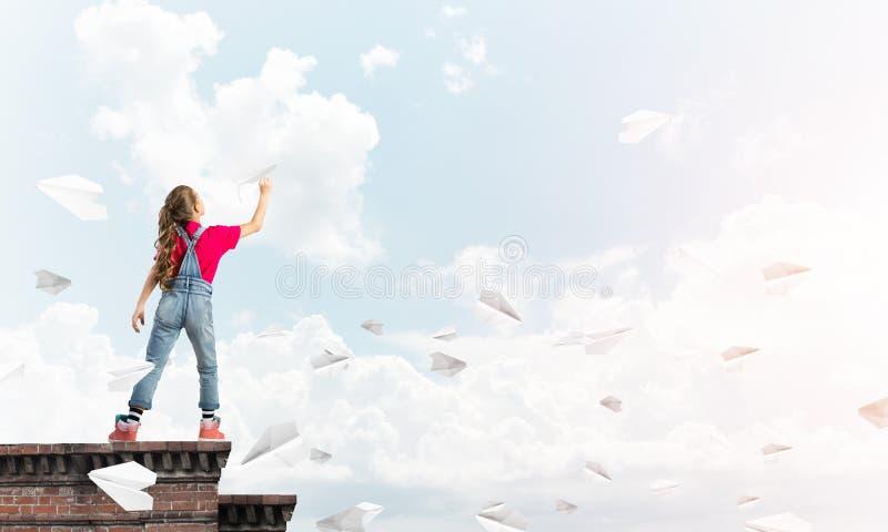 Concept achteloze gelukkige kinderjaren met meisje proef het dromen om te worden stock afbeelding