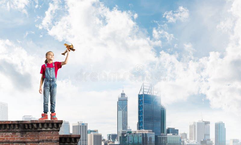 Concept achteloze gelukkige kinderjaren met meisje proef het dromen om te worden stock afbeeldingen