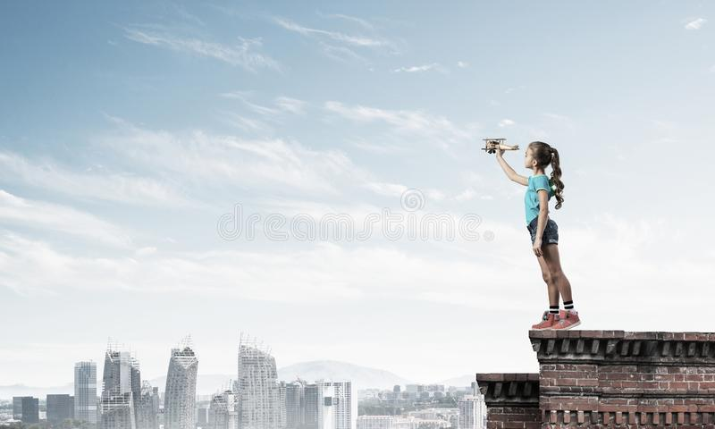 Concept achteloze gelukkige kinderjaren met meisje proef het dromen om te worden stock fotografie