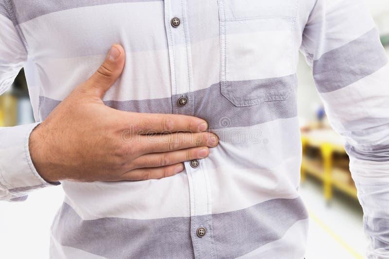 Concept acide gastrique avec l'homme pressant son estomac images stock