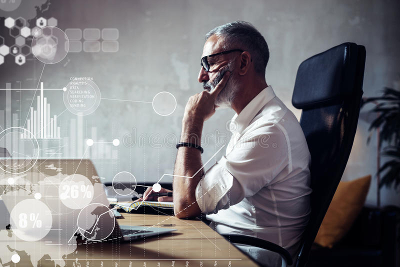Concept of adult bearded businessman making a great business decisions in modern workplace.Screen global virtual icon. Concept of adult bearded businessman royalty free stock image