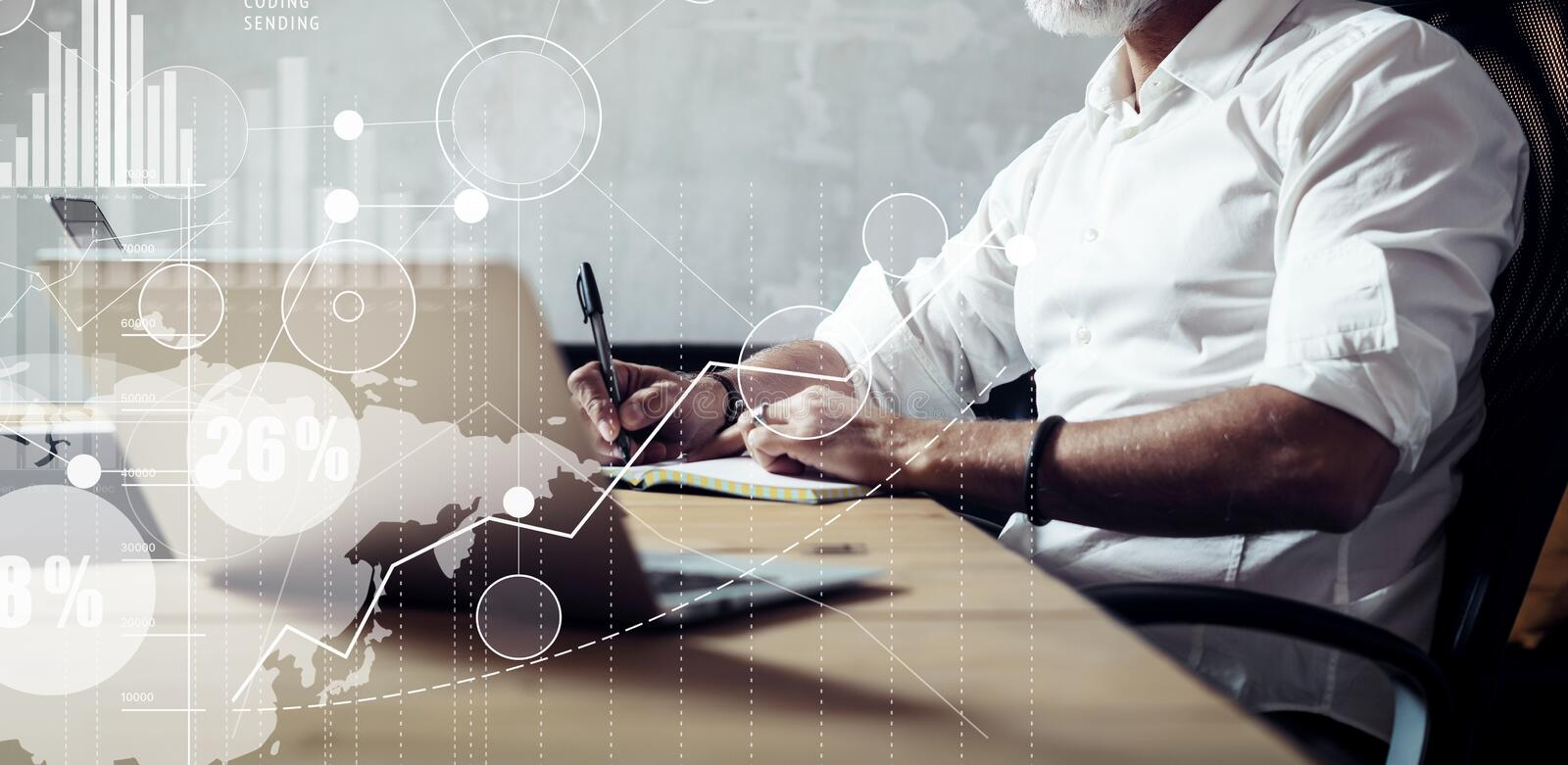 Concept of adult bearded businessman searching a great business solutions in modern workplace.Screen global virtual icon. Diagram and graph interfaces stock photo