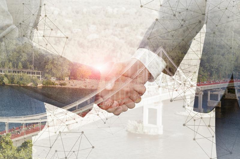 The concept of the agreements reached in the business. The concept of the agreements reached in the business. Handshake on the background of the bridge stock images