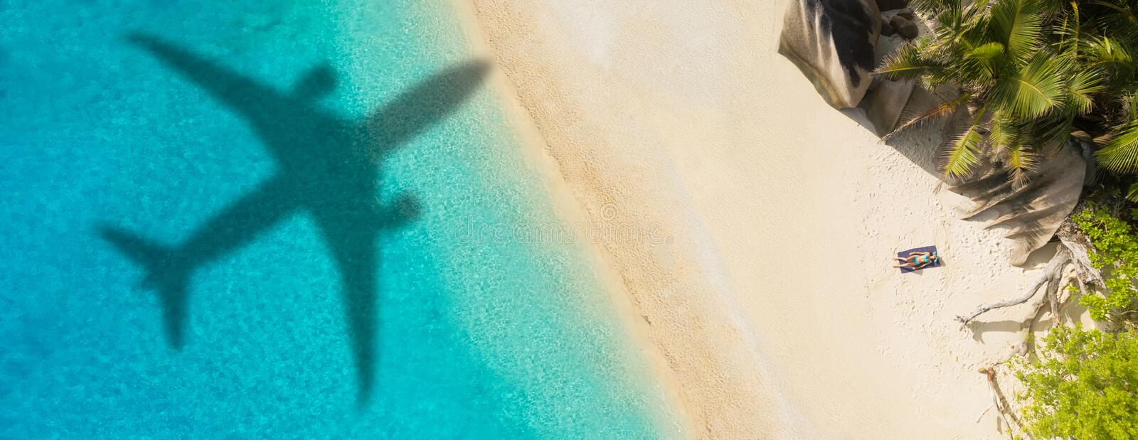 Concept of airplane travel to exotic destination. With shadow of commercial airplane flying above beautiful tropical beach. Beach holidays and travel stock photos