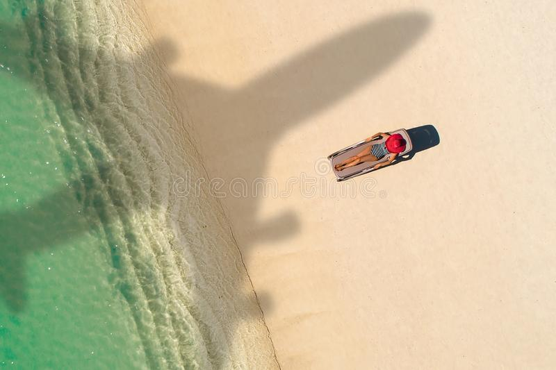 Concept of airplane travel to exotic destination with shadow of commercial airplane flying above beautiful tropical beach. Beach stock photo