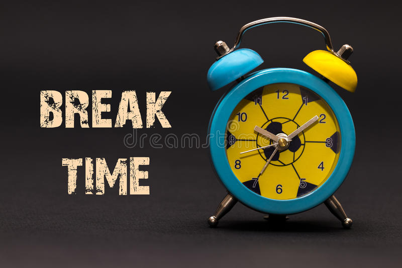 Concept,alarm clock with break time phrase written on black back royalty free stock photo