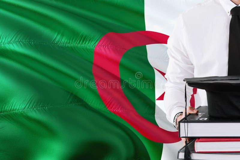 Concept algérien réussi d'éducation d'étudiant Tenir les livres et le chapeau d'obtention du diplôme au-dessus du fond de drapeau photographie stock