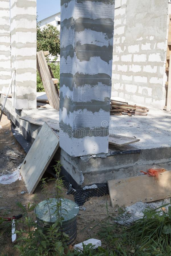 Concept of alteration of construction at customer`s request. Load-bearing columns made of foam block are taken out of  perimeter. Of foundation by 10 stock image