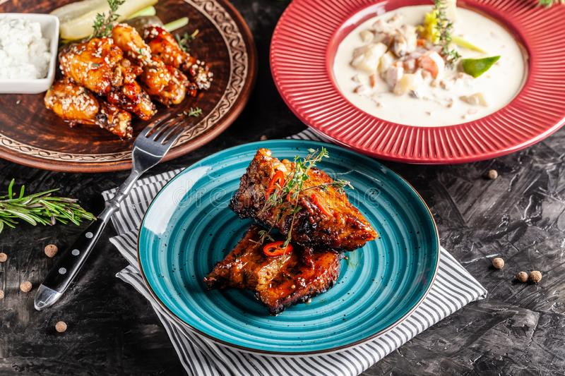 The concept of American cuisine. American dishes on the table. Meat, soup, glazed chicken wings. Background image royalty free stock image